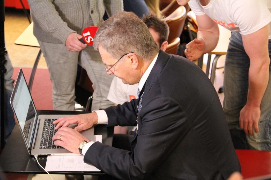 リアクターのインストラクターと取材陣に囲まれて、初めてのプログラミングに取り組むニーニスト大統領