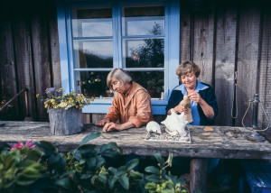 <写真左>ウラリンナ通りのアトリエで制作に励むトーベ。ここでほとんどのムーミンの物語が生まれました © Per Olov Jansson <写真右>左:トーベ・ヤンソンと右:グラフィックデザイナーであり、トーベの生涯のパートナーでもあるトゥーリッキ・ピエティラ。彼女はムーミンの物語の中ではトゥーティッキー(おしゃまさん)のモデルになっている © Per Olov Jansson